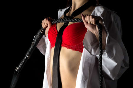 Photo of woman in mens shirt with whip on black background Stock Photo