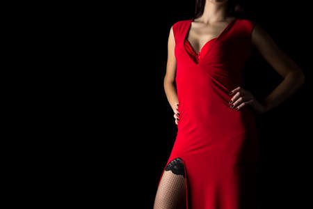 Photo of sexy woman in red dress on black background