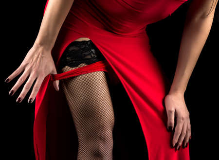 Woman taking off red panties on black background