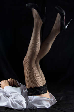 no face: Photo of woman raised legs up on black background