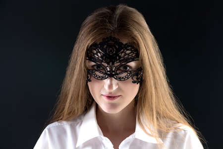 enigma: Portrait of cute woman in lace mask on black background