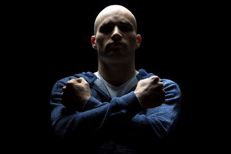 hairless: Photo of young hairless man in shadow with arms crossed on black background Stock Photo