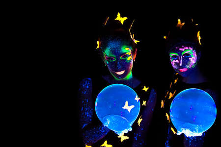 Portrait of two young woman with luminous make up and bubble in darkness photo