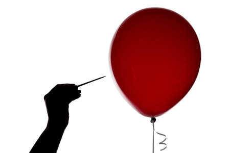 Silhouette of hand with the needle and red balloon on white background