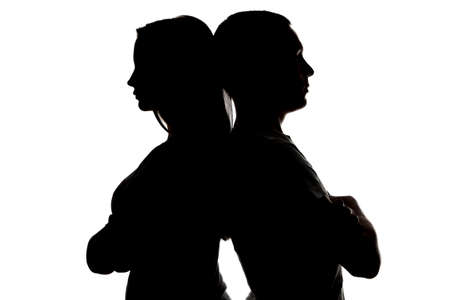 lovers quarrel: Photo of silhouette teenagers looking in different sides on white background Stock Photo
