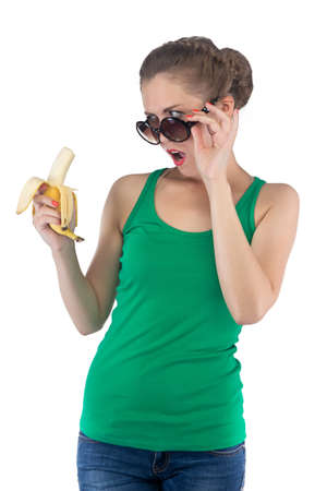 outrage: Photo of surprised girl with banana and sunglasses on white background Stock Photo