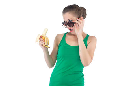 outrage: Image of surprised woman with banana and sunglasses on white background Stock Photo