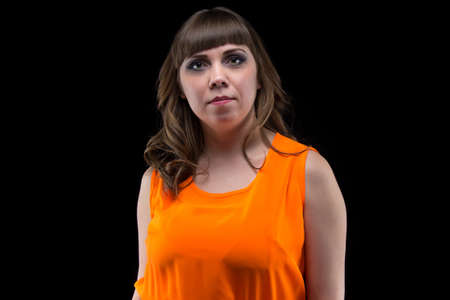 plump: Portrait of plump woman in orange dress on black background