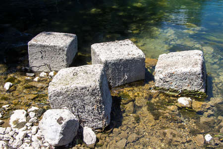 among: Photo of square stones among water in the summer Stock Photo