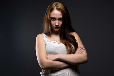 defenseless: Photo of brunette girl with crumpled shirt on black background Stock Photo