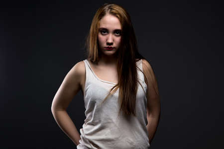 defenseless: Photo of pudgy girl with crumpled shirt on black background Stock Photo