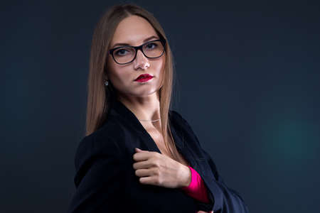 chest hair: Photo of serious woman in black jacket on black background