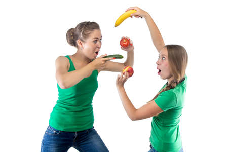women fighting: Photo of two women fighting fruits on white background