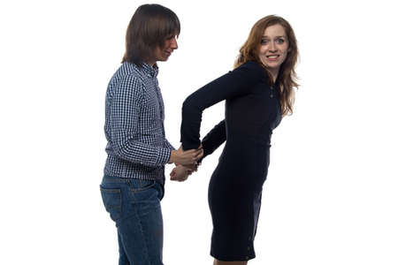 Man and young woman with pair of handcuffs on white background Stock Photo