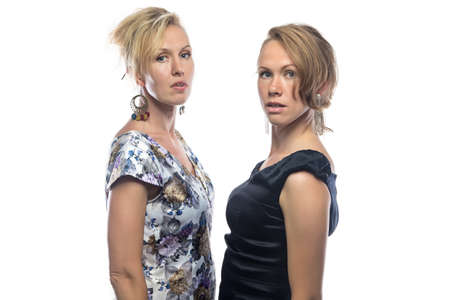 talk big: Two serious sisters on white background. Isolated photo on white background.