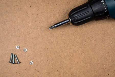 bolts and nuts: Bolts, nuts and electric screwdriver on fibreboard