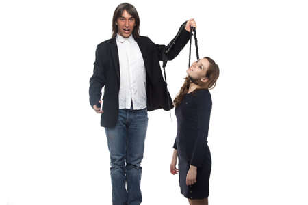 Man in black jacket holding woman with whip. Isolated photo with white background.
