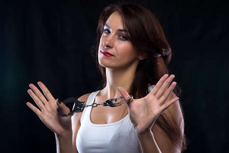 adult nude: Woman in t-shirt with handcuffs looking at camera. Portrait photo with black background.