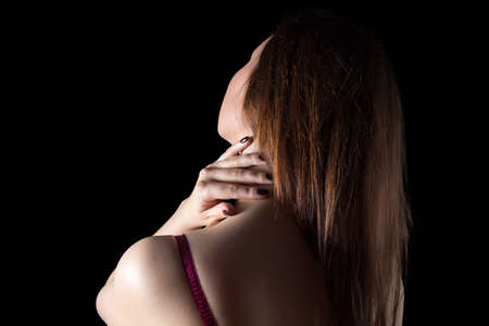 pink bra: Woman touching neck on black background. Photo of womans body in shadow.