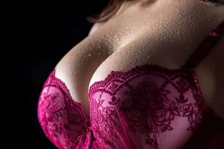 wet breast: Womans breast with drops on black. Photo of womans body in shadow. Stock Photo