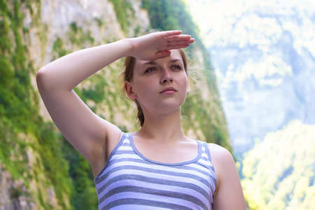 hand on forehead: Young woman with hand near forehead, in the mountains