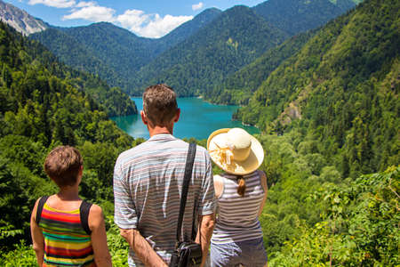Tourists looking at mountain lake among mountains