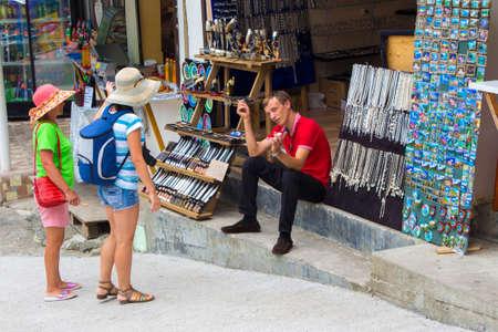 Women tourists in panama hats choose souvenir production