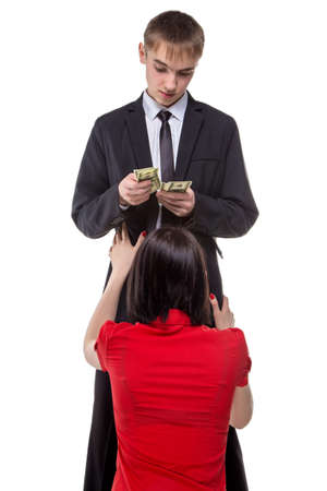 prostitution: Man counting money with woman on her knees. Isolated photo of people with white background.