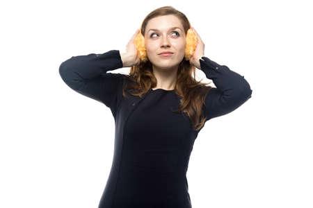 cabello rubio: Mujer desconcertada con los auriculares de invierno, aislado en fondo blanco Foto de archivo