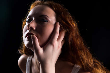 arousal: Pretty woman with red hair and mans hand on black background