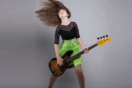 headbang: Teenage girl with guitar, shaked head on grey background