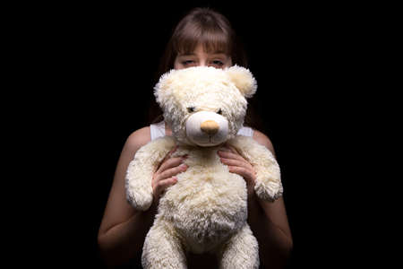 deceptive: Cunning teenage girl with teddy bear on black background Stock Photo