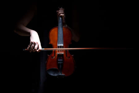 instrumentalist: Woman playing on violin on black background