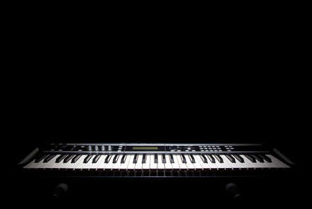 Piano in shadow, music on black background Standard-Bild