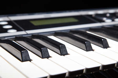 music background: Piano keyboard in shadow, music on black background Stock Photo