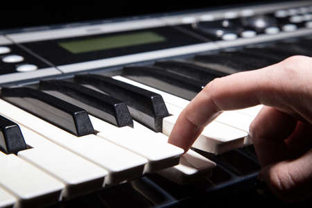 music background: Playing on piano keyboard on black background Stock Photo