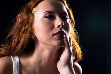 arousal: Pretty woman with red hair on black background