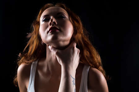 arousal: Woman with red hair and mans hand on black background