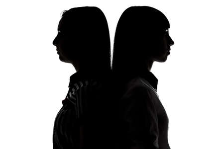 spat: Silhouette of women standing back to back on white background Stock Photo