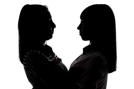 Silhouette of women looking at each other on white background