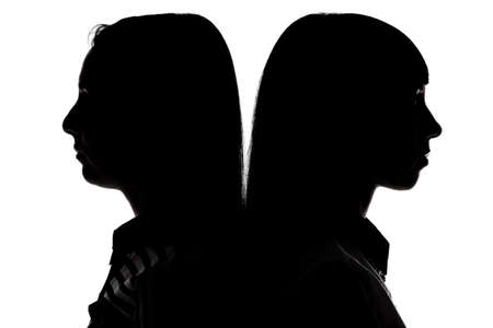 spat: Women standing back to back on white background Stock Photo
