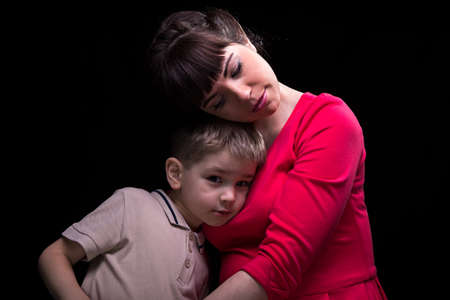 maternal: Gentle mother and little son on black background