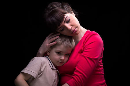 Gentle hugging mother and little son on black background Stock Photo