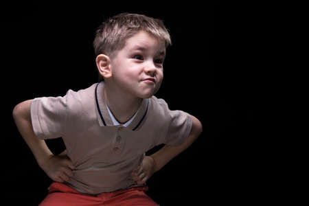 disobedient child: Little grimacing boy with hands on hips on black background Stock Photo