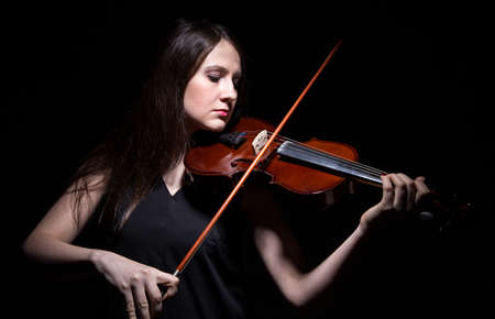 fiddle: Brunette woman playing on fiddle on black background Stock Photo