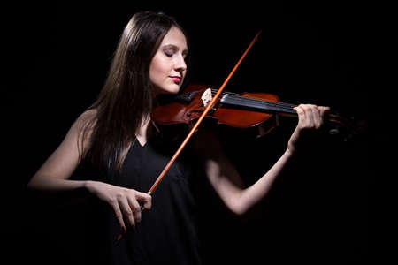 fiddlestick: Smiling woman playing on violin on black background Stock Photo