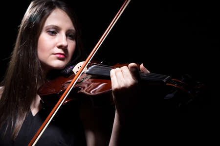 fiddler: Serious woman playing on violin on black background