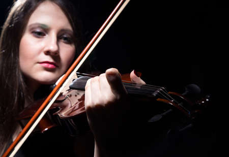 fiddler: Serious woman playing on violin, close up on black background