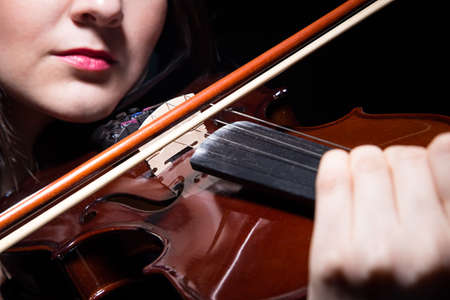 fiddles: Woman playing on violin, close up on black background