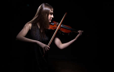 fiddle: Young woman playing on fiddle on black background